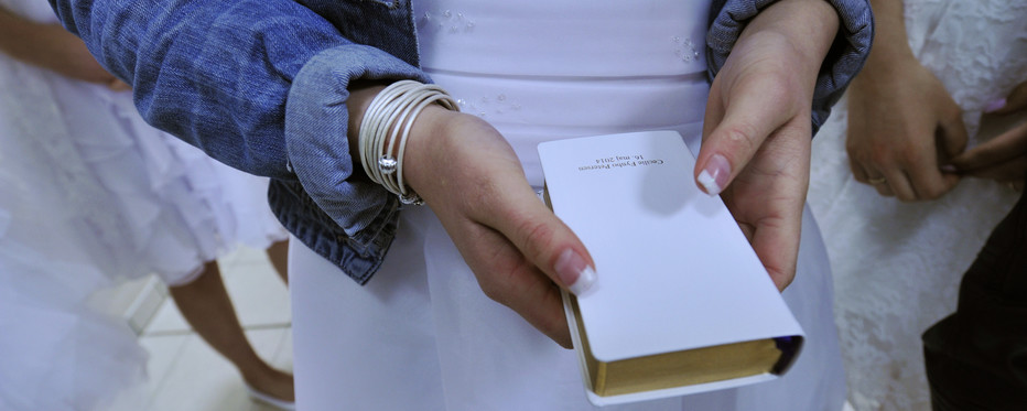 Konfirmand står med salmebog i hånden