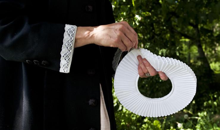 Præst holder sin præstekrave i hånden