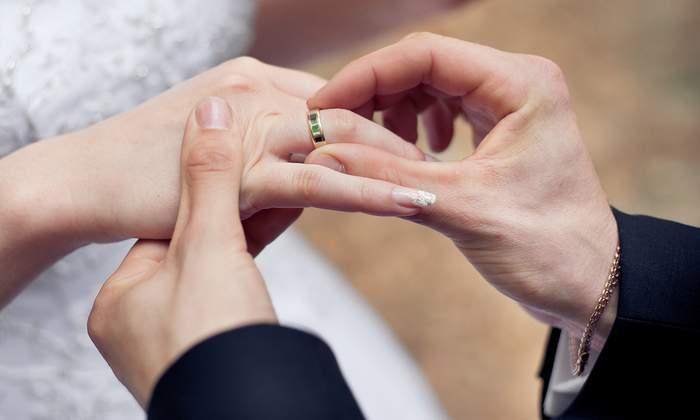 Gommen sætter vielsesring på brudens finger