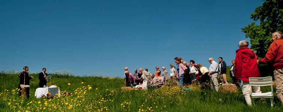 Folk samles i det fri på en  mark til friluftsgudstjeneste