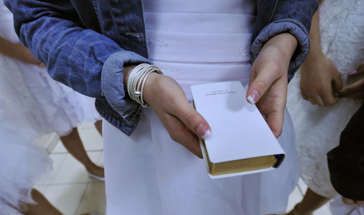 Konfirmand med salmebog i hånden