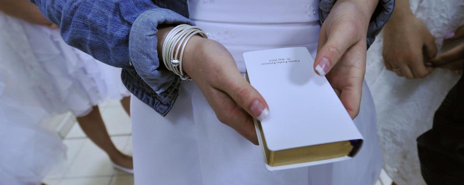 Konfirmand står med sin salmebog