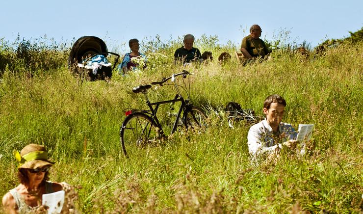 Folk sidder spredt i græsset med læsepapir i hånden